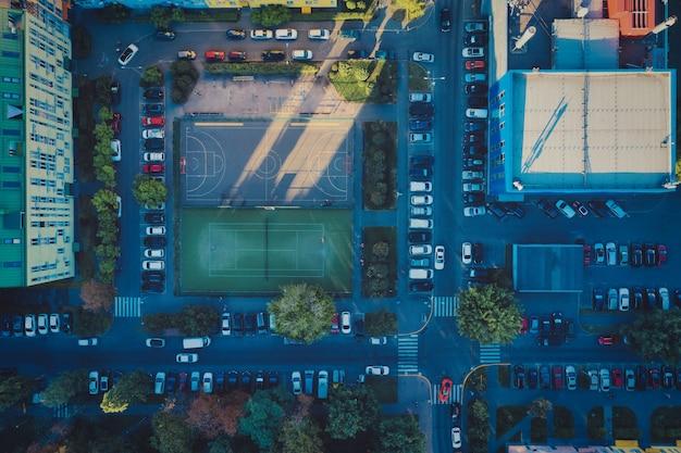 Boisko do piłki nożnej i kort tenisowy w dzielnicy mieszkalnej obok zaparkowanych samochodów