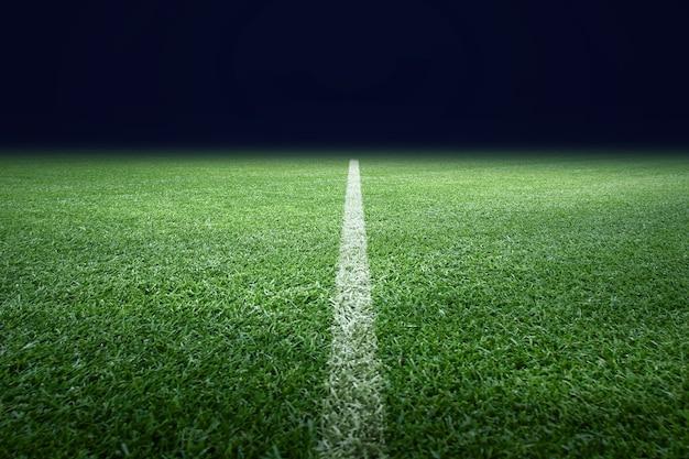 Boisko do piłki nożnej z zieloną trawą. tło trawnika sportowego