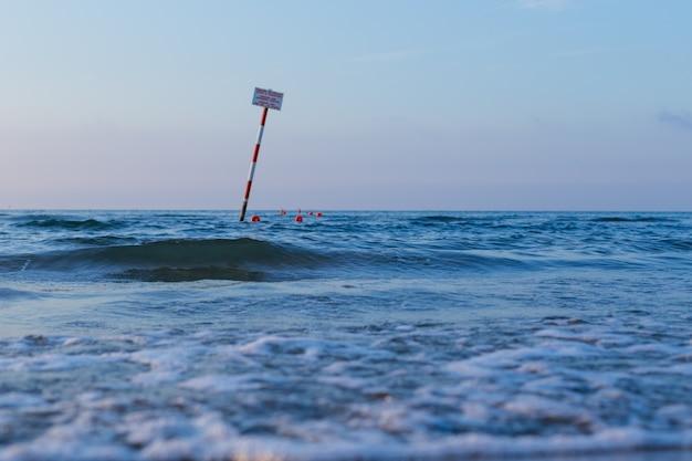 Boja unosi się na wodzie morskiej. boja przykuty do dna morskiego pod wodą i kołyszący się na falach