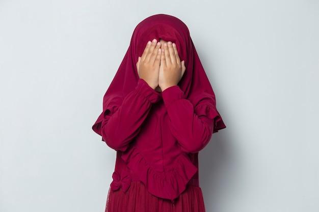 Bojąca się azjatycka muzułmańska dziewczynka zakrywa twarz rękami na białym tle