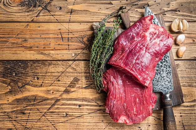 Bok steki surowej wołowiny na desce do krojenia rzeźnika z nożem. drewniane tła. widok z góry. skopiuj miejsce.