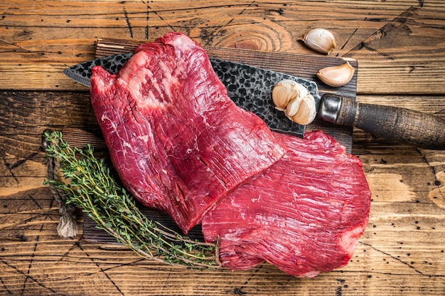 Bok steki surowej wołowiny na desce do krojenia rzeźnika z nożem. drewniane tła. widok z góry.