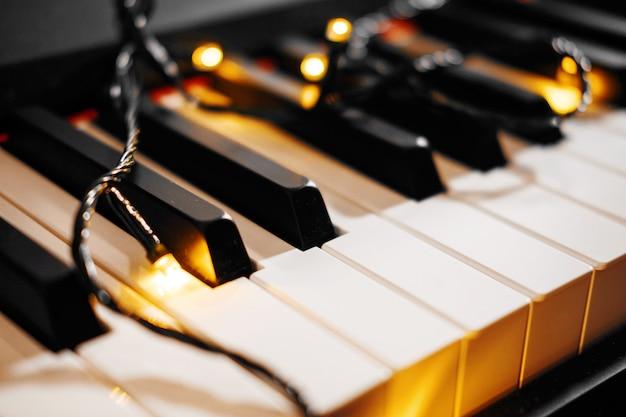Bokeh klawiszy fortepianu z lampkami choinkowymi na pokładzie nowego roku fortepianu