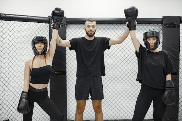 Boks kobiet. sędzia ogłasza zwycięzcę. pani w czarnej sportowej odzieży. kobiety z trenerem.