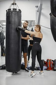 Boks kobieta. początkujący na siłowni. pani w czarnej sportowej odzieży. kobieta z trenerem.