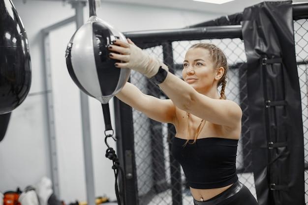 Boks kobieta. początkujący na siłowni. pani w czarnej sportowej odzieży.