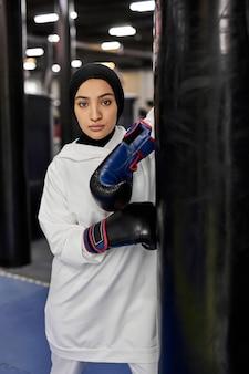 Boks sportowiec muzułmańska kobieta w białym hidżabie lub islamskim sportowym stroju stojącym przez worek treningowy, arabska dopasowana kobieta w rękawicach bokserskich patrząc na kamery z poważną twarzą. kryty na siłowni