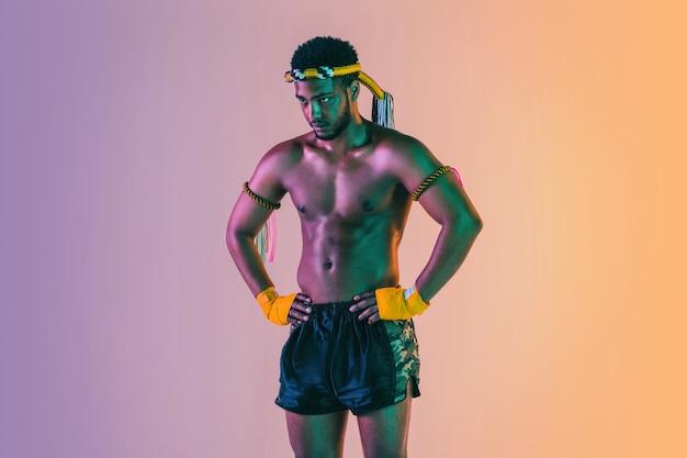 Boks tajski. młody człowiek ćwiczeń boksu tajskiego na ścianie gradientowej w świetle neonowym. zawodnik pozujący pewnie, trenujący sztuki walki w akcji, ruchu. zdrowy styl życia, sport, koncepcja kultury azjatyckiej.