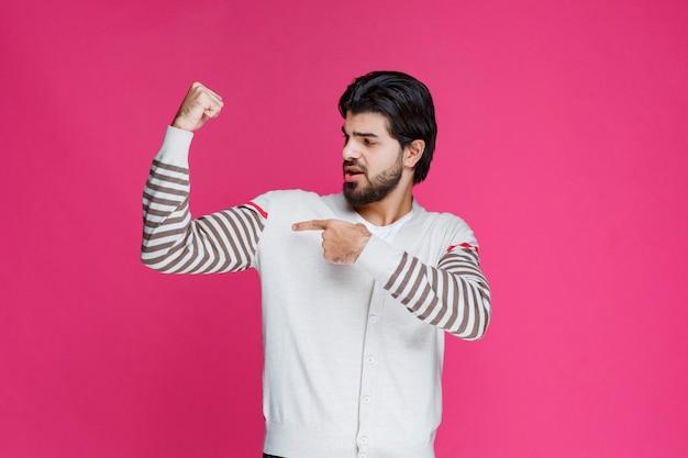 Bokser demonstrujący swoje bicepsy i czujący się potężny.