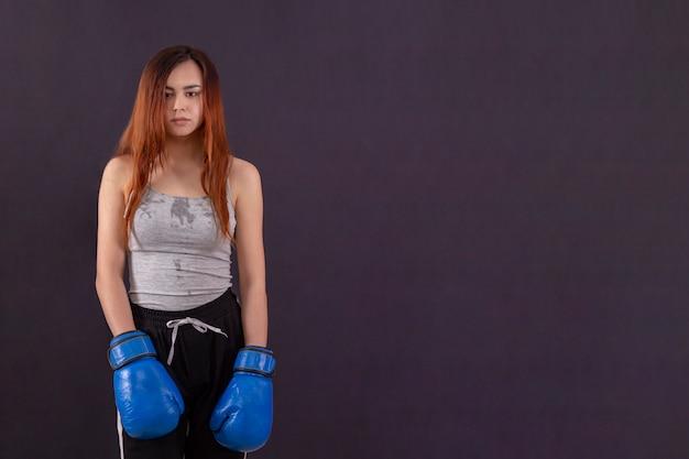 Bokser kobieta w rękawicach bokserskich zmęczony i spocony po treningu
