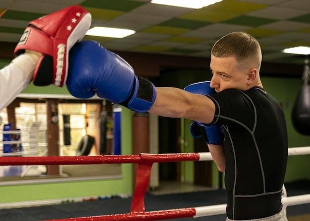 Bokser mężczyzna w rękawiczkach ćwiczy z trenerem