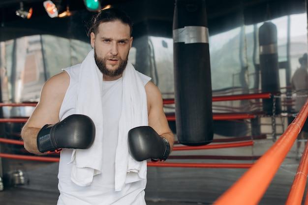 Bokser po treningu na ringu. portret spoconego sportowego boksera na sobie bandaże bokserskie