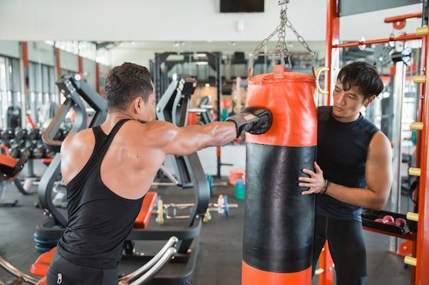 Bokser robi trening na worek treningowy z trenerem