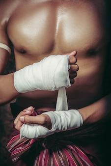 Bokser siedział na kamieniu, zawiązał taśmę wokół dłoni i przygotowywał się do walki.