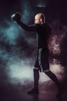 Bokser sportowca walczący na czarnej przestrzeni z dymem