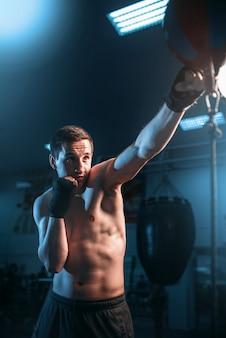 Bokser w bandażach, trening z torbą na siłowni