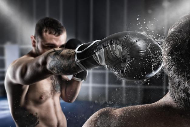 Bokser w zawodach bokserskich bije przeciwnika ciosem