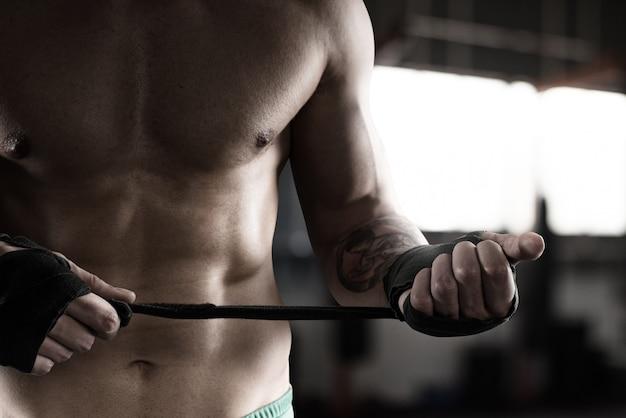 Bokser z tatuażami i mięśniami zakłada taśmy na dłonie