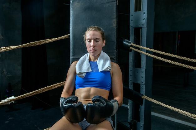 Bokser z zamkniętymi oczami odpoczywa po walce bokserskiej