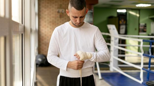Bokser zawijający ręce przed treningiem w ringu wstążką