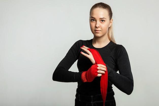 Bokserka owija dłonie czerwonymi opakowaniami bokserskimi. pojedynczo na białym tle z miejscem na tekst