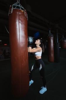 Bokserska kobieta pozuje z uderzać pięścią torbę na zmroku. silna i niezależna koncepcja kobiety