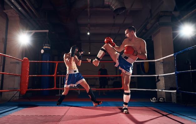 Bokserzy trenujący kickboxing na ringu w klubie zdrowia