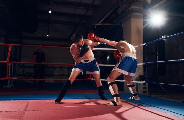 Bokserzy trenujący kickboxing na ringu