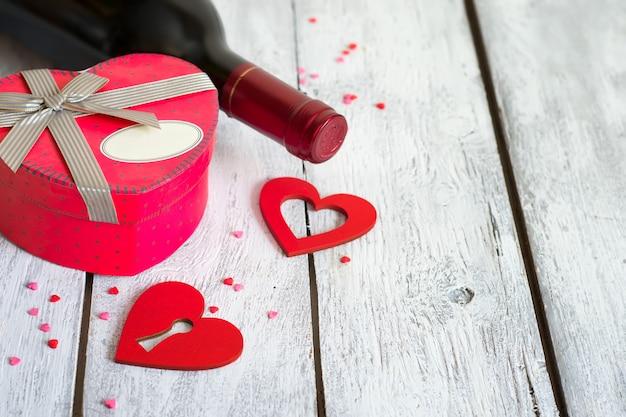 Boksuje w kształcie serca i butelki czerwonego wina na białym tle. koncepcja walentynki