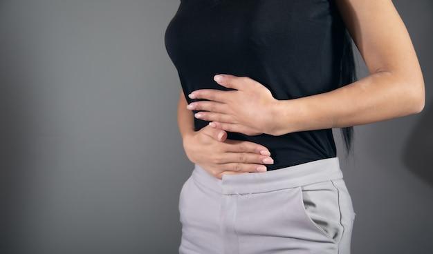 Ból brzucha kobiety z powodu zapalenia żołądka lub miesiączki