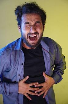 Ból brzucha obrazuje mężczyznę, który ma problemy z żołądkiem.