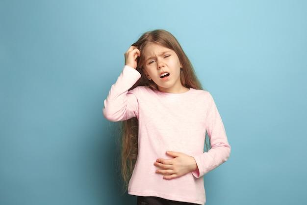 Ból brzucha. smutna dziewczyna z bólem brzucha na niebieskim tle studia. wyraz twarzy i koncepcja emocji ludzi. modne kolory. przedni widok. portret do połowy długości