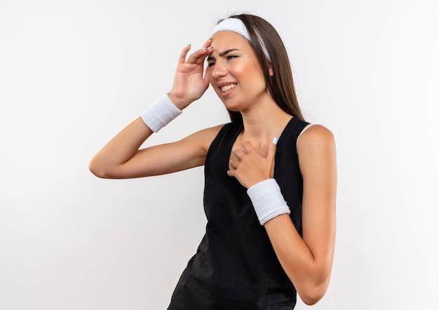 Ból całkiem sportowy dziewczyna nosi opaskę i nadgarstek, kładąc rękę na głowie i na klatce piersiowej patrząc na bok na białym tle na białej ścianie