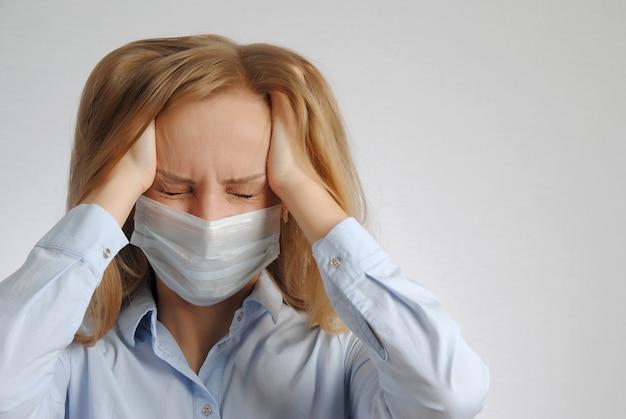 Ból, cierpienie i frustracja kobiety trzyma głowę w masce medycznej