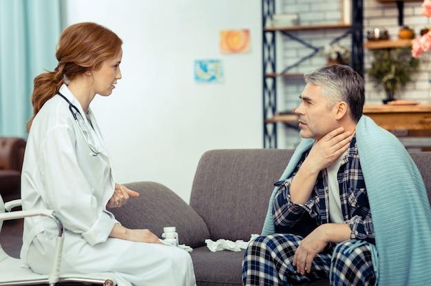 Ból gardła. miły, posępny mężczyzna dotyka szyi i skarży się lekarzowi na ból gardła