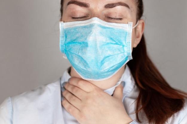 Ból gardła. młoda dziewczyna w masce medycznej czuje się źle.