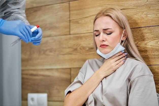 Ból gardła w sezonie koronawirusowym grypy. kobieta dotyka szyi i odczuwa ból siedząc w sypialni w domu, podczas gdy lekarz przygotowuje się do badania lekarskiego, cierpi na objawy covid-19.