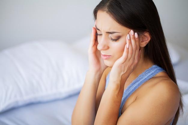 Ból głowy. atrakcyjna młoda kobieta budzi się na łóżku patrząc nieszczęśliwy i chory.