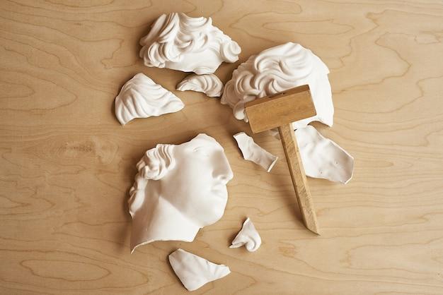 Ból głowy, choroba psychiczna, koncepcja depresji. złamana głowica gipsowa z drewnianym młotkiem.
