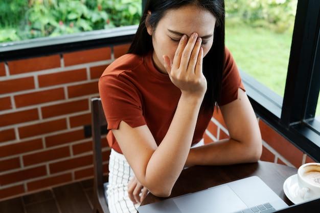 Ból głowy kobiety po długim pracy na laptopie