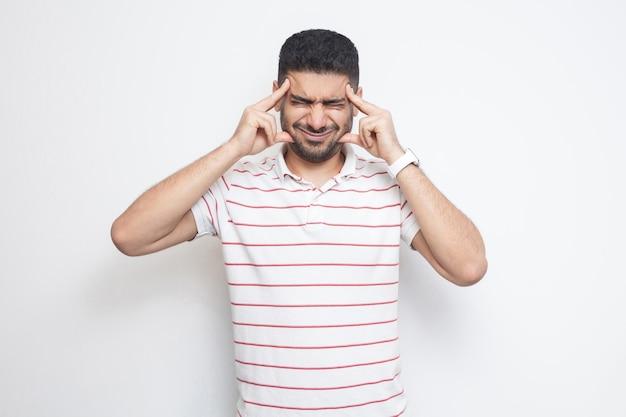 Ból głowy lub konfuzja. portret zdezorientowanego przystojnego brodatego młodzieńca w pasiastym t-shirtie, stojącego, trzymającego za bolesną głowę lub myślącego. kryty strzał studio, na białym tle.