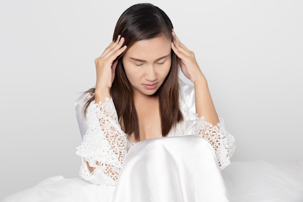 Ból głowy, na szarym tle, kobiety w białej koszuli nocnej i satynowej szacie z długim rękawem z kwiecistą koronkową zawrotami głowy aż do bezsenności na białym łóżku w sypialni.