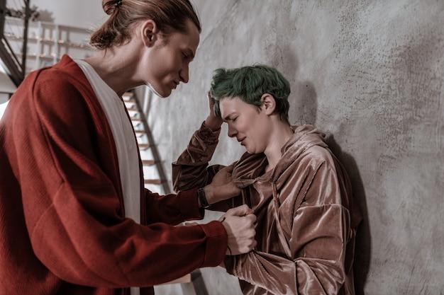 Ból głowy po uderzeniu. młoda zielonowłosa kobieta ma ból głowy po kolejnym uderzeniu chłopaka