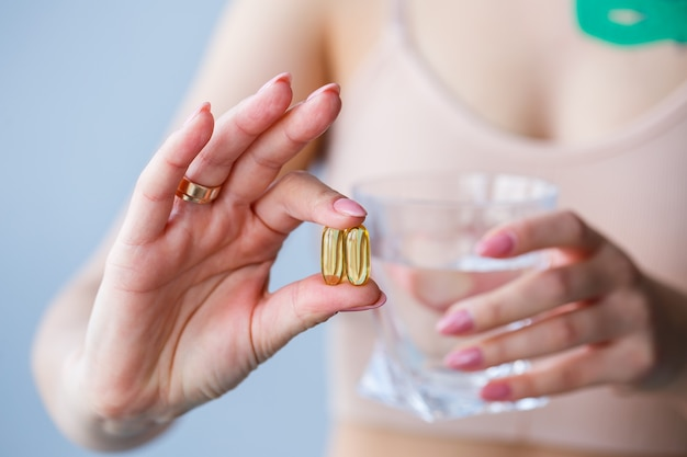 Ból głowy, ręka z tabletkami. kobieta zażywa lekarstwa popijając szklanką wody. dzienna wartość witamin, skutecznych leków, nowoczesnej apteki dla koncepcji zdrowia ciała i zdrowia psychicznego.