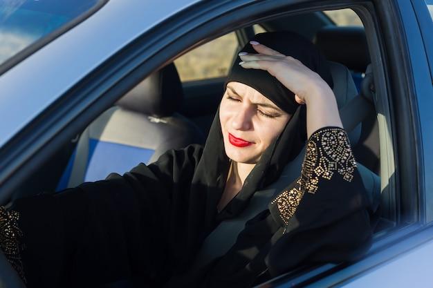Ból głowy u kierowcy kobiety siedzącej w samochodzie.