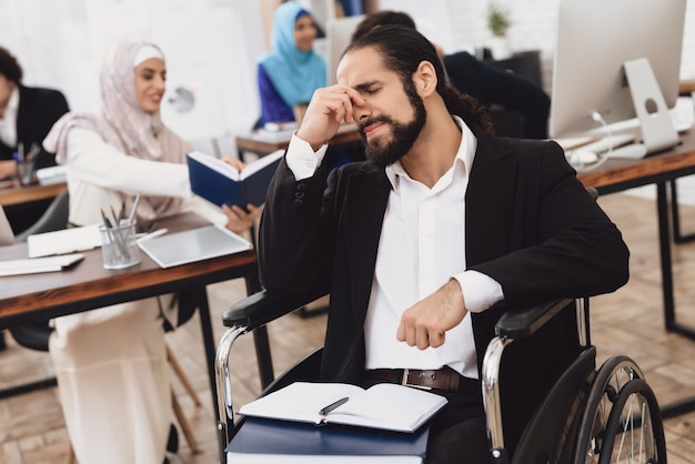 Ból głowy w biurze niepełnosprawny mężczyzna na wózku inwalidzkim.