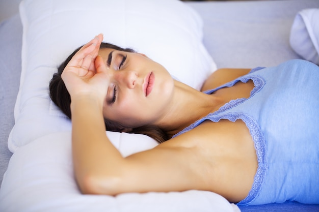 Bół głowy. zmęczona, wyczerpana młoda kobieta, która cierpi na silny ból głowy. portret pięknej chorej dziewczyny cierpiącej na migrenę, uczucie presji i stresu