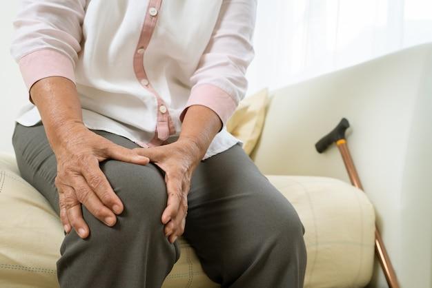 Ból kolana starej kobiety w domu, problem opieki zdrowotnej starszy koncepcji