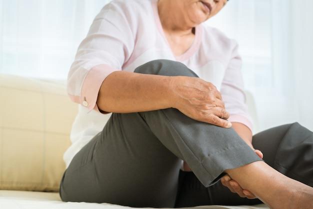 Ból nogi starszej kobiety w domu, problem opieki zdrowotnej starszy pojęcie