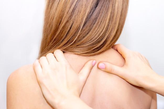 Ból pleców. ręczny masaż pleców i szyi. masaż i pielęgnacja ciała. spa masaż ciała kobieta ręce leczenie.